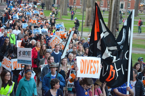 Divest Harvard activists and supporters march through Harvard Yard