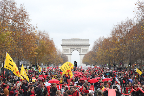 "On the last day of the Paris summit, activists draw ""climate red lines"" in front of the Arc de Triomph"