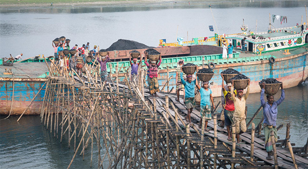 People unload baskets of coal out of a boat in Bangladesh