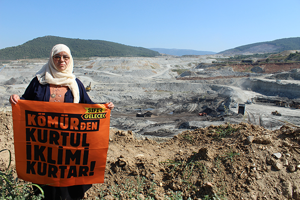 Woman stands at edge of giant coal mine