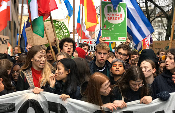 Teenagers and young adults with banner at front of march, country flags behind
