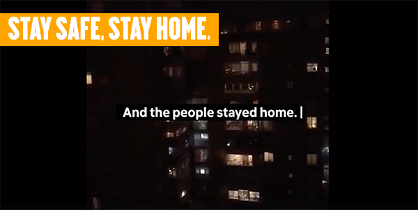 An apartment building facade at night with lit windows and the words stay safe, stay home